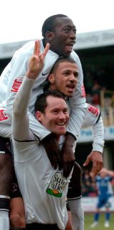 Hereford United's hat-rick hero Steve Guinan (bottom) celebrates with teamates Lionel Ainsworth and Toumani Diagouraga.